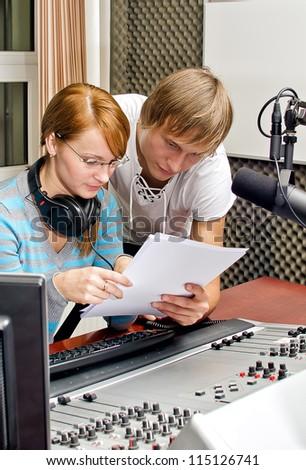 Colleagues examine broadcast list in studio - stock photo