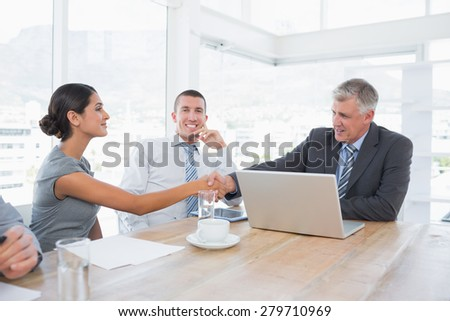 Colleagues greeting each other in the office - stock photo