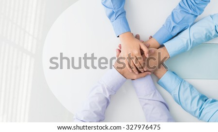 Colleagues heaping their hands anticipating new project - stock photo