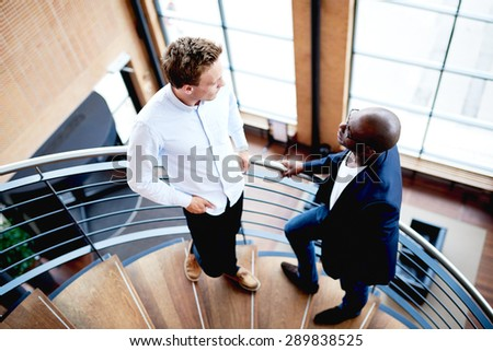 Colleagues interacting at work standing on spiral staircase in modern building. - stock photo
