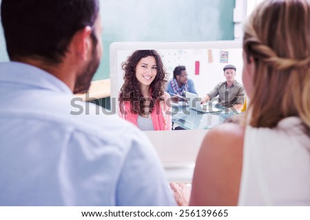 Colleagues looking at computer against smiling woman with creative team working behind - stock photo
