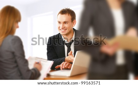 colleagues looking at laptop screen in office