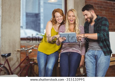 Colleagues looking towards digital tablet while leaning on desk in creative office
