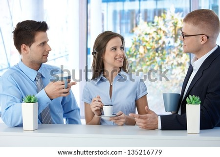 Colleagues on coffee break in business office, talking and smiling. - stock photo
