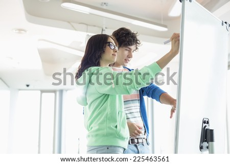 Colleagues preparing presentation on whiteboard in creative office - stock photo