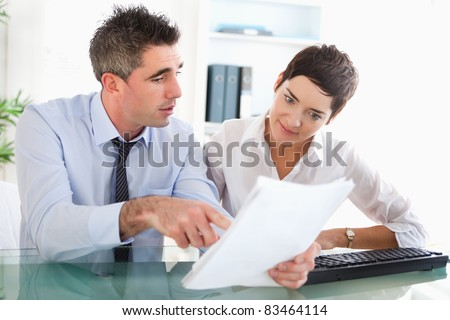 Colleagues reading documents in an office - stock photo