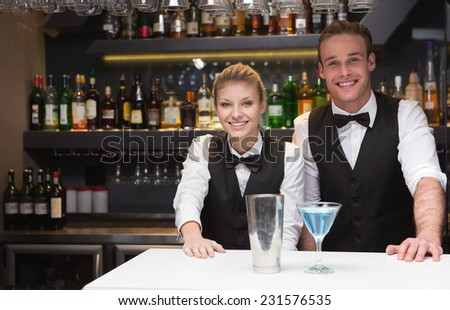 Colleagues smiling at the camera in a bar - stock photo