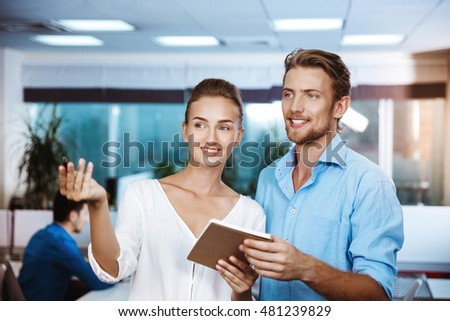 Colleagues smiling, speaking, holding notebook, over office background.