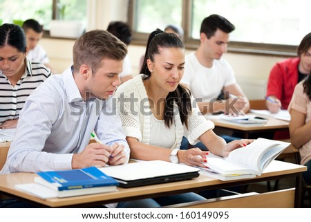 colleagues students studying together in classroom  - stock photo