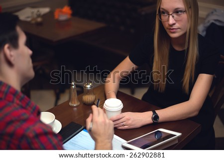 Colleagues talking during lunch drinking cofee and staring at each other. - stock photo