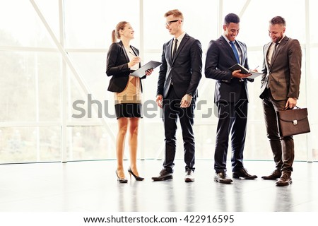 Colleagues talking in corridor - stock photo