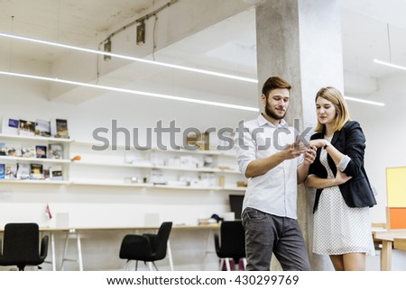 Colleagues using phone in an office and talking - stock photo