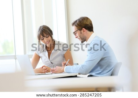 Colleagues working in modern office with laptop - stock photo