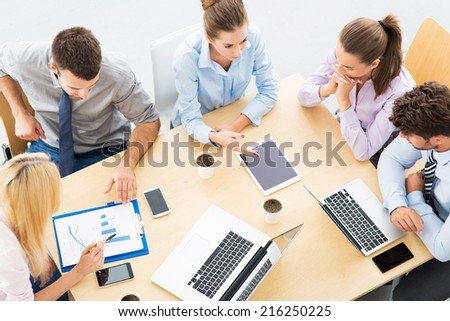 Colleagues working in office, high angle - stock photo