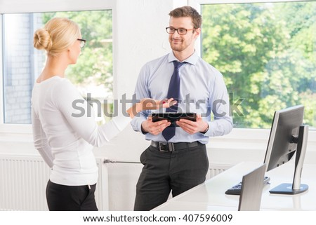 Colleagues working in the office with a tablet. - stock photo