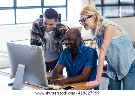 Colleagues working on computer together in the office - stock photo