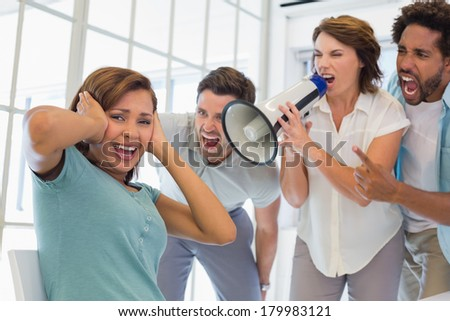 Colleagues yelling through a megaphone at businesswoman in the office - stock photo