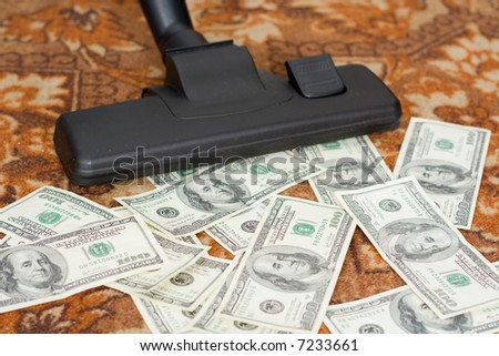 Collecting by a vacuum cleaner from a floor of money - stock photo
