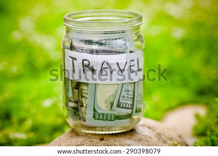 Collecting money for travel. Glass tin as moneybox with cash savings (banknotes )  - stock photo