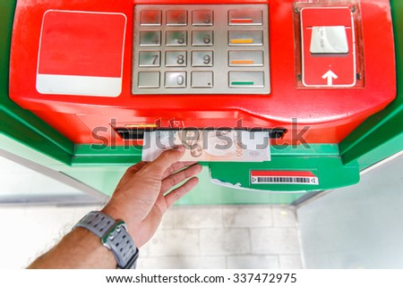 Collecting thai 1000 baht notes at ATM machine. - stock photo