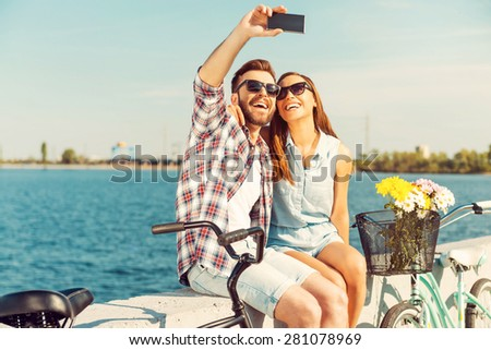Collecting the bright moments. Smiling young couple making selfie while sitting on parapet near their bicycles  - stock photo