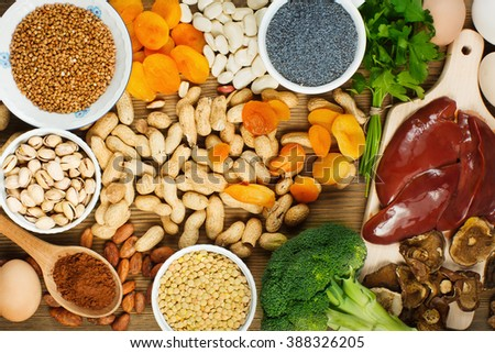 Collection iron rich foods as liver, buckwheat, eggs, parsley leaves,dried apricots, cocoa, lentil, bean, blue poppy seed, broccoli, dried mushrooms, peanuts and pistachios on wooden table. - stock photo