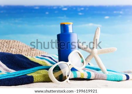 Collection of beach items - lotion, starfish, beautiful towel, sunglasses - stock photo