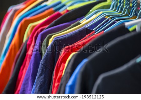 Collection of colored shirts on hangers - stock photo