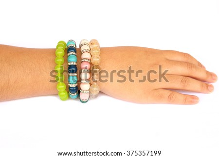 Collection of colorful bracelets stone on woman hand isolated on white background