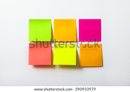 Collection of colorful post it paper note on white background. Multi-colored sticks hanging on the board - stock photo
