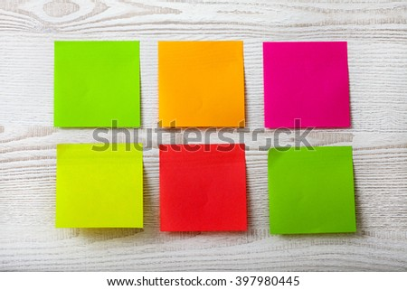 collection of colorful post it paper note on white wooden background - stock photo