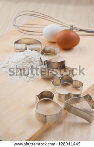 collection of Cookie cutter forms around flour on wooden board with whisk