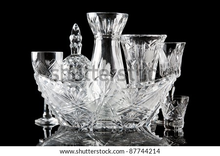 collection of crystal dishes isolated on a black background - stock photo
