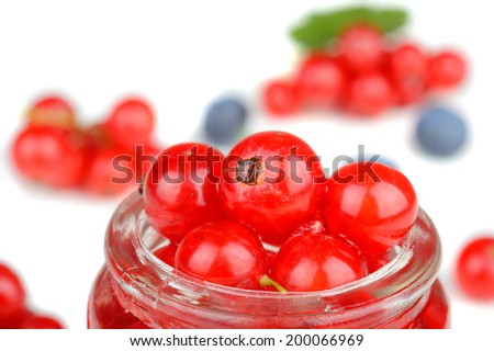 Collection of delicious fresh red currant berries, some of them in a small glass jar, in a studio setting - stock photo