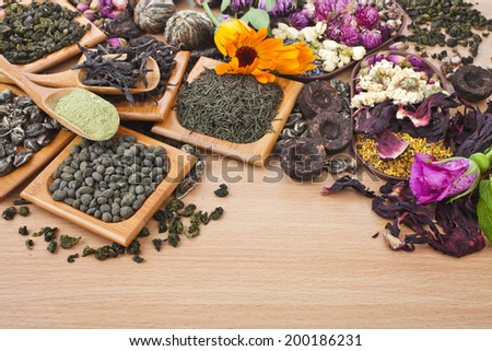 Collection of different dry types tea (green,black, herbal) in spoon on kitchen wooden table background,  top view - stock photo