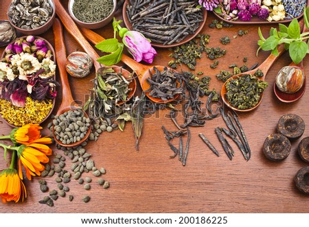 Collection of different  types tea (green,black, herbal) in wooden spoon on kitchen red wooden table background,  top view - stock photo