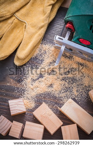 Collection of electric fretsaw sawdust leather safety gloves and wooden studs on vintage wood background construction concept.