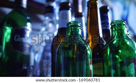 Collection of empty alcohol bottles in several colors ready for recycling. - stock photo