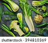Collection of fresh green vegetables placed on black stone - stock photo