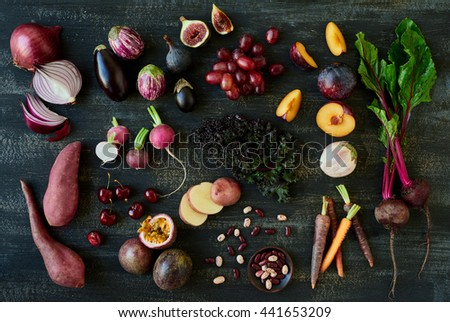 Collection of fresh purple toned vegetables and fruits on dark rustic distressed background, heirloom carrots, beetroot, fig, aubergine, grapes, radishes, loose leaf lettuce, kale, beans
