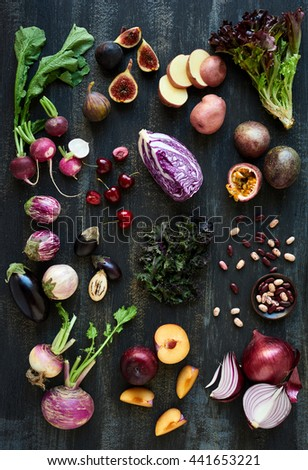 Collection of fresh purple toned vegetables and fruits on dark rustic distressed background, heirloom eggplant, fig, aubergine, cherries, radishes, lettuce, beans passionfruit, cabbage, plum, onion - stock photo