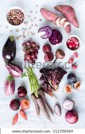 Collection of fresh purple toned vegetables and fruits on white rustic background, eggplant, beetroot, carrot, fig, plum, aubergine, cabbage, grapes, radishes, loose leaf lettuce - stock photo