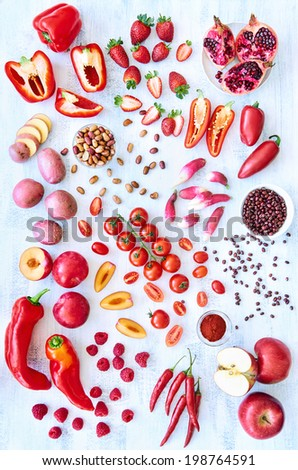Collection of fresh red toned vegetables and fruits raw produce on white rustic background, peppers capsicum chilli strawberry raspberry pomegranate tomato paprika azuki beans plum - stock photo