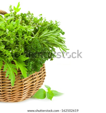 Collection of Fresh Spicy Herbs in Basket / isolated on white / thyme, basil, oregano, parsley, marjoram, rucola, sage and rosemary herbs / Vertical composition - stock photo