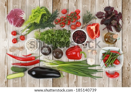 Collection of fresh vegetables on white wood background, eggplant, parsley, white beans, tomatoes, parsley, beets, peppers, garlic, onions, cucumbers, red beans, thyme, salt, cabbage - stock photo