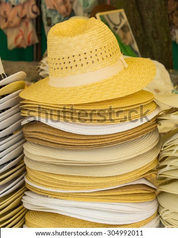 Collection of handmade straw hats on stall at the bazaar, summer fashion, head protection - stock photo