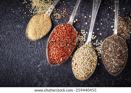 collection of healthy seeds in silver spoons on dark background - stock photo