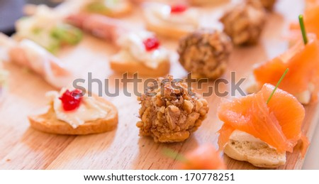 Collection of Hors D'oeuvres on a wooden platter - stock photo