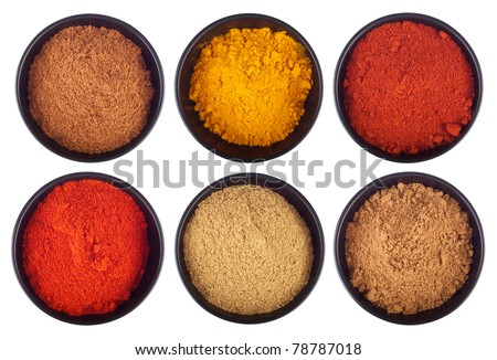 collection of indian spices (cumin, coriander, paprika, garam masala, curcuma, chili powder) on black ceramic cups isolated on white background - stock photo