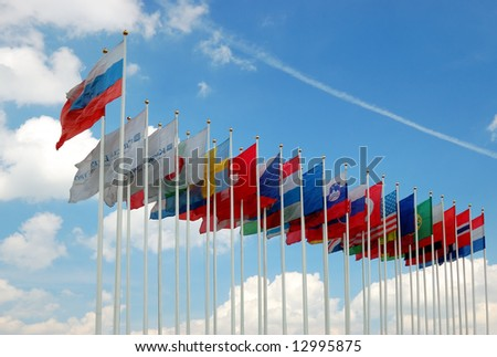 Collection of international flags over a cloudy blue sky - stock photo